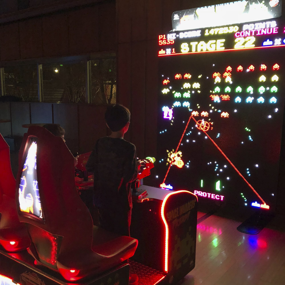 two kids playing giant led space invaders
