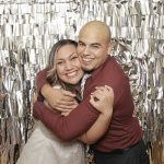 couple in photo booth with silver backdrop hugging
