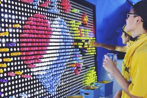 man smiling at giant lite brite design at pepsi event