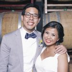 groom and bride in photo booth in front of wine barrel backdrop