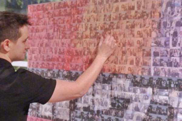 man placing image on photo mosaic wall