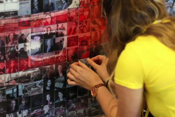 woman placing images on mosaic wall